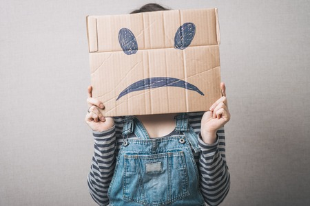 Young woman standing with a cardboard on his head with sad face