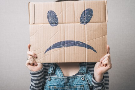 masquerader: Young woman standing with a cardboard on his head with sad face