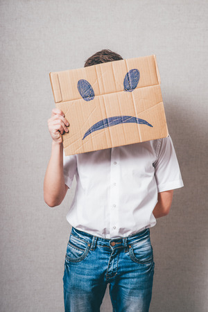 sad face: Putting a smiling face on. Man holding cardboard paper with smiley face printed on as sadness sorrow. Stock Photo