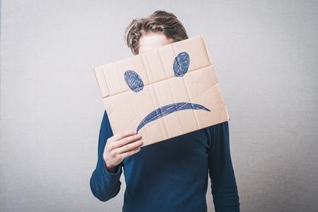 homme triste: Jeune homme avec un carton sur la tête avec le visage triste Banque d'images