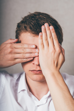 closes eyes: young man closes his eyes with his hands Stock Photo