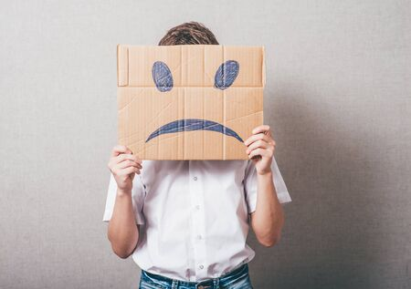 masquerader: Putting a smiling face on. Man holding cardboard paper with smiley face printed on as sadness sorrow. Stock Photo