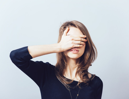 hide and seek: woman covering her eyes isolated on a gray background