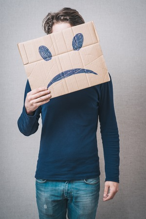 masquerader: Young man with a cardboard on his head with sad face