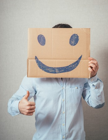 man, holding a picture with a cheerful smiley