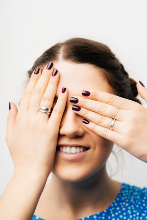 closes eyes: young girl closes eyes with her hands Stock Photo