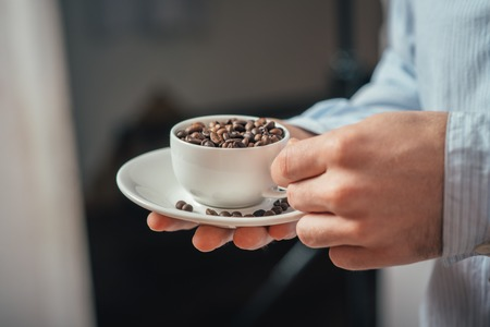 Cup of coffee beans. Young man holding a cup of coffee beans in his hands.
