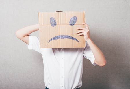 Putting a smiling face on. Man holding cardboard paper with smiley face printed on as sadness sorrow. Фото со стока