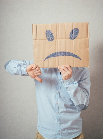anonym: Young man with an unhappy smiley card half covering face Stock Photo