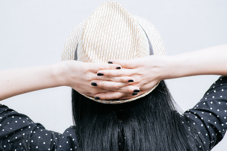 girl in hat put hands behind her head