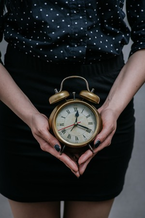 Woman showing alarm clock. On a gray background.