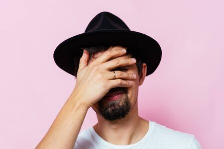 man covers his face by hand Archivio Fotografico