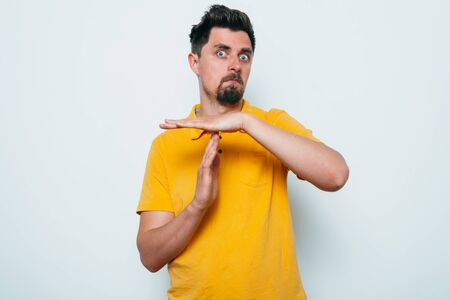 A man shows the hands stop timeout. On a gray background. Stock Photo