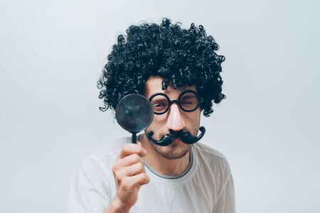 A man in a wig and funny glasses with a magnifying glass 版權商用圖片