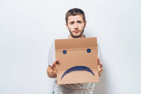 man  holding a picture with a unhappy smiley Stok Fotoğraf