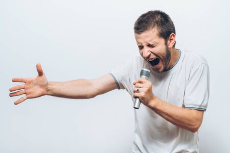 Boy Rocking Out. Image of a handsome man singing to the microphone. Emotional portrait of an attractive guy