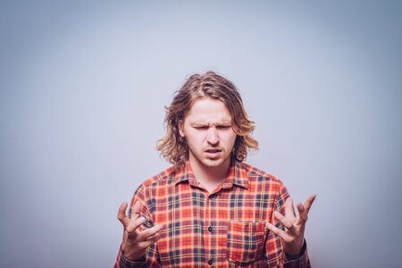 portrait of pissed off young adult man, hands in air Stock Photo