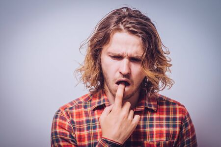 male of European appearance causes vomiting putting his fingers in his mouth on a gray background, nausea Stock Photo