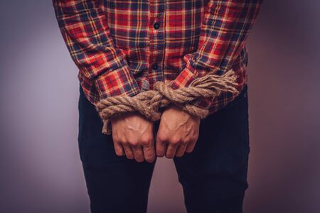 Tortured business man holding his hands tied with a rope