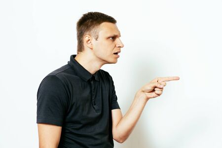 Closeup side view portrait of young man, pointing with finger at someone or something. Positive human face expressions, emotions, feelings, attitude, approach