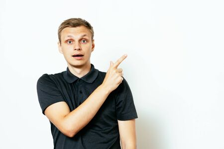 young man, pointing with finger at someone or something. Positive human face expressions, emotions, feelings, attitude, approach