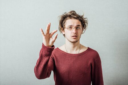 The man in glasses showing a little bit, a little. On a gray background. Stock fotó