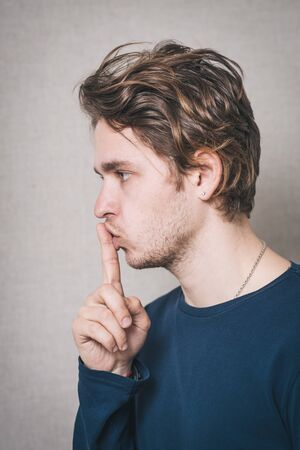 A man shows a finger to his mouth quiet. On a gray background.