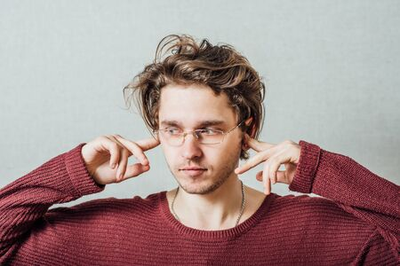 Closeup portrait young, angry, unhappy, stressed man covering his ears, looking up, to say, stop making loud noise its giving headache. Negative emotions, face expressions Stock Photo