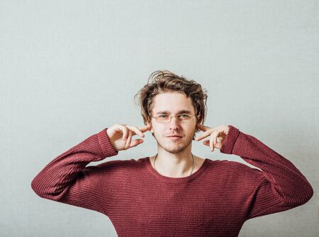 Closeup portrait young, angry, unhappy, stressed man covering his ears, looking up, to say, stop making loud noise it's giving headache. Negative emotions, face expressions Stock Photo