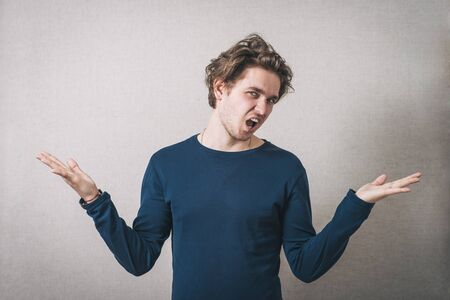 Man angry, shouts, lifting his hands up. Gray background Stock Photo
