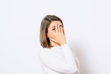 The woman covers her face with her hands and peeps