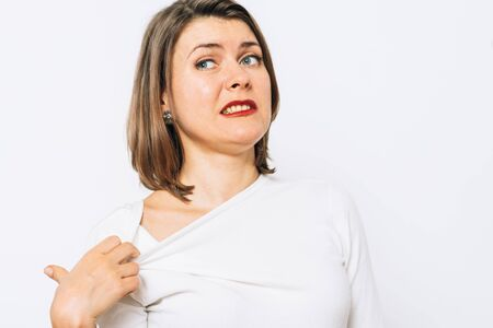 Close-up portrait of a young woman opening shirt to express that hot. Negative emotions, expressing, feeling