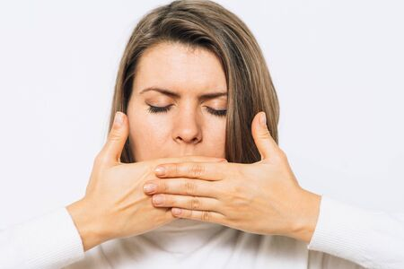 Successful stylish girl covers her mouth with her hands, isolated in the studio