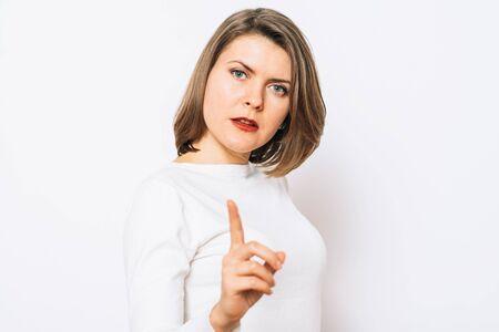 studio portrait of a beautiful girl pointing to the camera 版權商用圖片