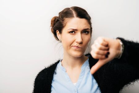 Woman offended or upset lowered thumb down. Isolated on a white background Banco de Imagens