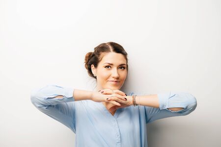 Woman near the face with fists, thinking. Isolated on a white background