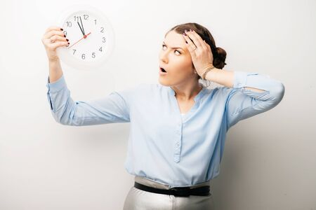 Woman with clock and hand on head dissatisfied, angry late. Isolated on a white background