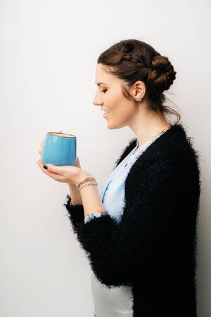 Woman with big blue cup, drink tea or coffee. Profile. Isolated on a white background
