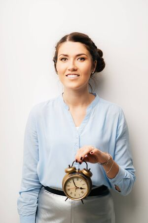 Woman with a clock in hands. Isolated on a white background