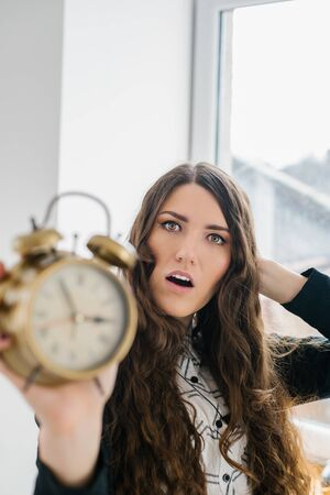 Closeup portrait woman extending hand to alarm clock. Human face expression, emotion, feeling. 版權商用圖片