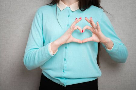 Happy smiling beautiful young woman showing heart symbol gesture, isolated 版權商用圖片