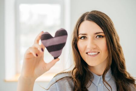 Picture of a small white heart in hands, female holds handmade sewn soft toy, woman with Valentine gift against the window, happy girl smiling, conceptual image of health care or love. 版權商用圖片