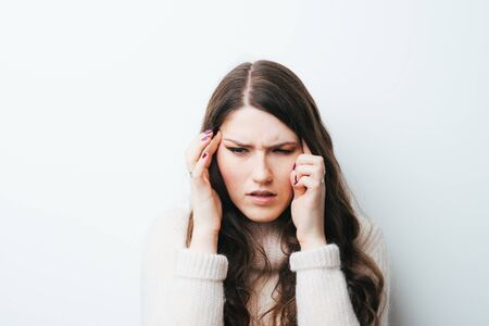 Young woman holding her head in pain suffering from a headache on a white background
