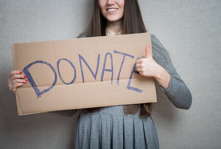 young woman showing board with text: Donate