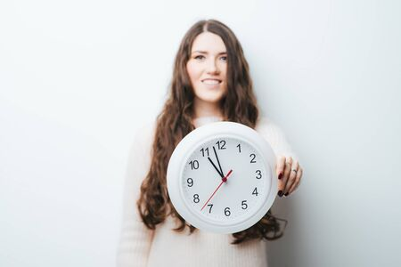 on a white background girl holding a clock in his hands