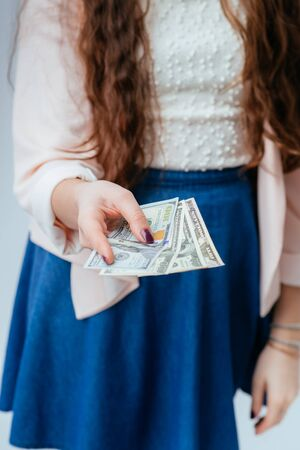 long-haired beautiful young brunette woman in blue long dress holds money in hands, received salary and considers