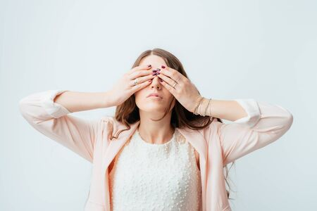 young woman covering her eyes with her hands