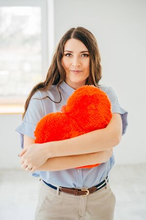Portrait of a  beautiful young brunette hugging red heart shaped pillow  against the window. 版權商用圖片