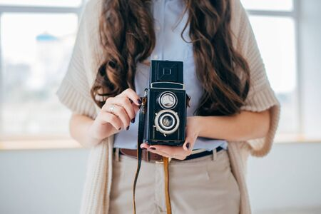 on a white background young girl with long hair with an old camera
