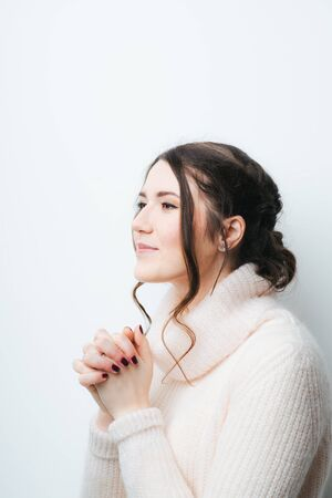 brunette girl praying and looking at the sky on a white background 版權商用圖片